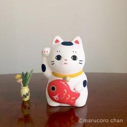 Artisanat japonais en céramique représentant un manekineko et une carpe koï.